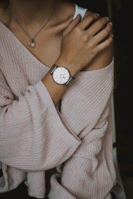 Dame met roze sweater aan die een subtiel zilveren calvin klein horloge draagt