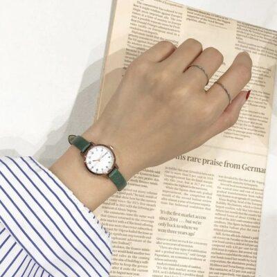 Vrouw di een horloge draagt en een wit overhemd met blauwe strepen met een arm die ligt op een krant