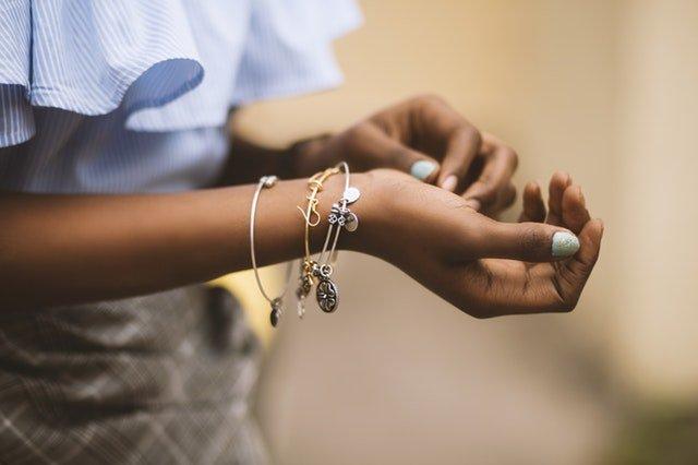 Een vrouw met een blauwe blouse met 3 verschillende armbanden om haar pols